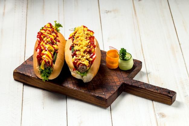 Deliciosos hot dogs con salsa de tomate y mostaza sobre fondo blanco.