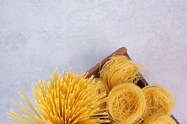 Deliciosos macarrones y fideos crudos en cuencos de madera