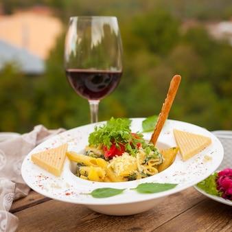 Deliciosos macarrones mezclados con ensalada con vino y queso en un plato con pueblo en el fondo, vista lateral.
