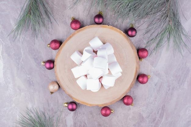 Deliciosos malvaviscos en una tabla de madera con bolas de roble alrededor