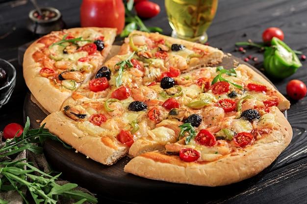 Deliciosos mariscos camarones y mejillones pizza en una mesa de madera negra. comida italiana.