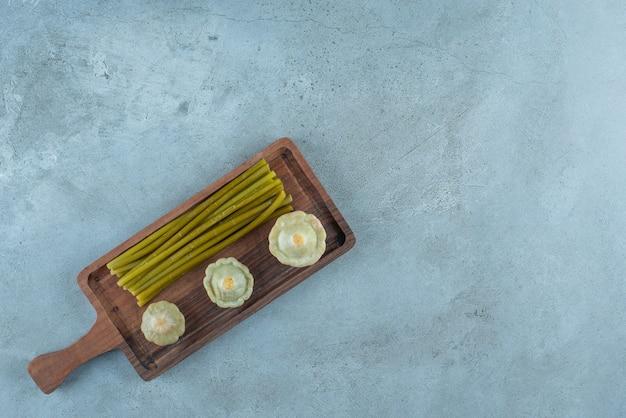 Deliciosos mini calabacines en escabeche y palos sobre una tabla, sobre la mesa de mármol.