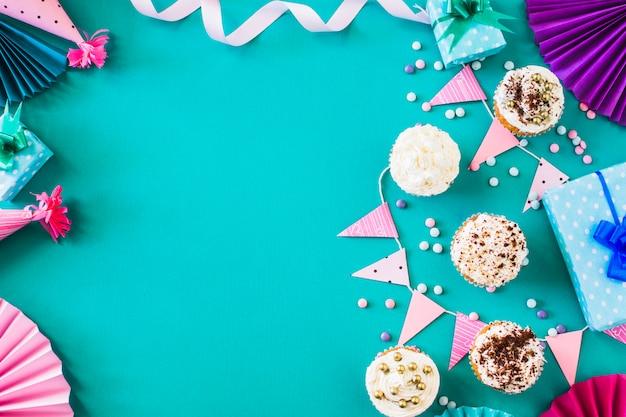 Deliciosos muffins con accesorios de fiesta en superficie verde.