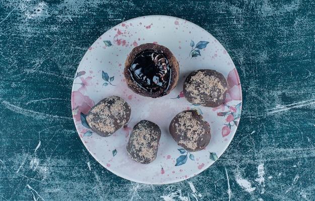 Deliciosos muffins de chocolate en el plato, sobre el fondo azul.