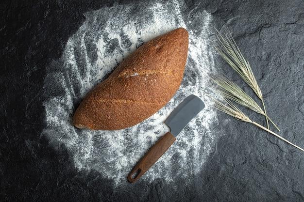 Deliciosos panes frescos sobre fondo blanco con cuchillo