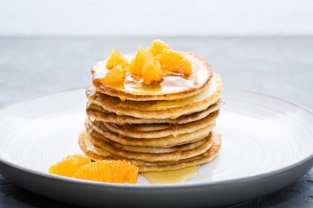 Deliciosos panqueques caseros con mandarinas y miel en un plato sobre la mesa.