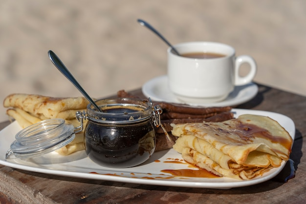 Deliciosos panqueques con miel de mangle y una taza de té blanco sobre la mesa, de cerca