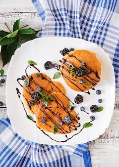 Deliciosos panqueques con moras y chocolate.