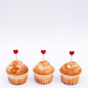 Deliciosos pasteles con adornos de corazones en varitas.