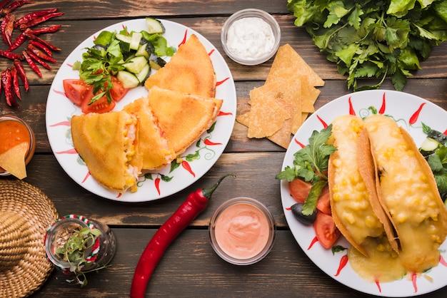 Deliciosos pasteles cerca de ensaladas de verduras en platos entre salsas y chili