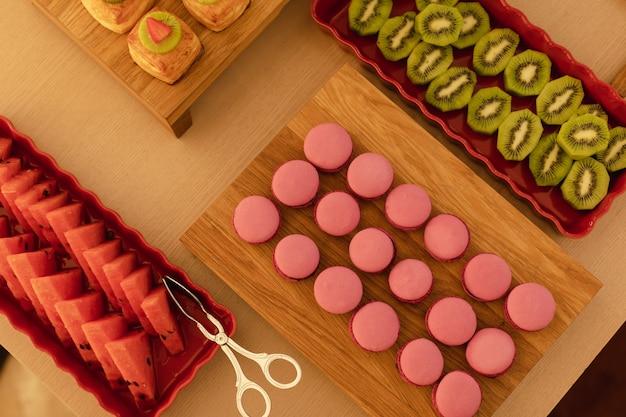 Deliciosos pasteles y frutas servidos en mesa de madera