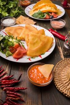 Deliciosos pasteles junto a ensaladas de verduras en platos entre nachos con salsas