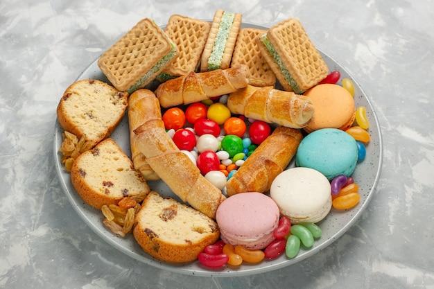 Deliciosos pasteles con macarons y caramelos en mesa blanca