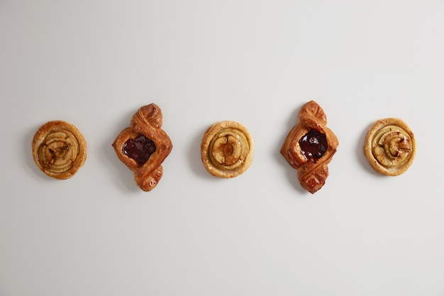 Deliciosos pasteles o galletas rellenas de mermelada, repostería recién horneada. hornear panecillos domésticos. tortas para el té en el desayuno. productos altos en calorías, gastronomía, panadería y concepto de tentación dulce.
