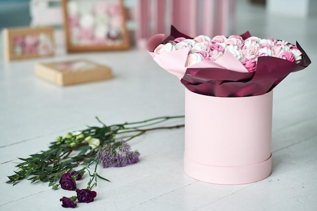 Deliciosos pasteles o merengues o malvaviscos en primer plano de la caja de regalo.