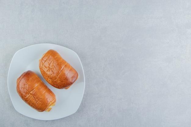 Deliciosos pasteles con salchichas en plato blanco.