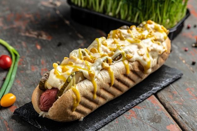 Deliciosos perritos calientes a la parrilla en un restaurante, salchichas caseras envueltas perritos calientes con queso y maíz. banner, menú, lugar de recetas para texto, vista superior