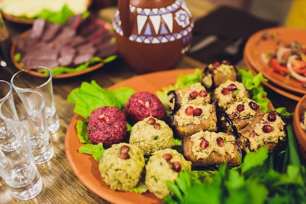 Los deliciosos platos de la mesa de la cocina georgiana, mucha comida deliciosa, vino, frutas y carne asada.