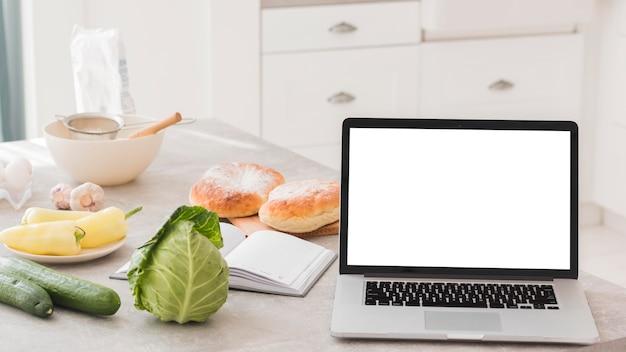 Deliciosos productos lácteos y vegetales con laptop