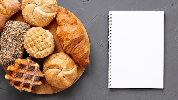 Deliciosos productos de pastelería y un cuaderno