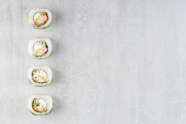 Deliciosos rollos de sushi con atún en mesa de piedra.