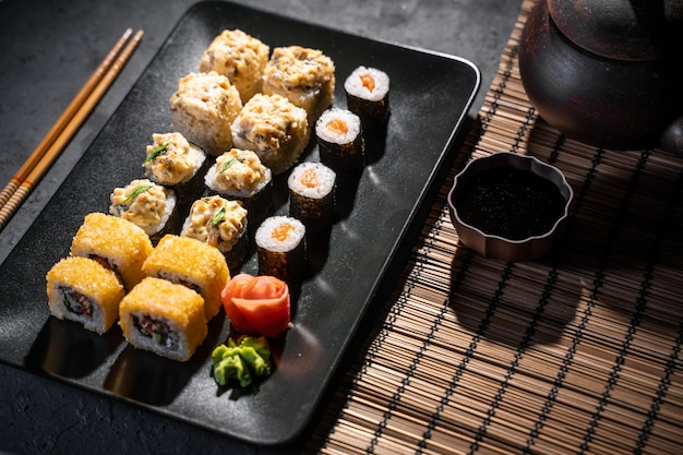 Deliciosos rollos de sushi servidos en mesa negra con palillos