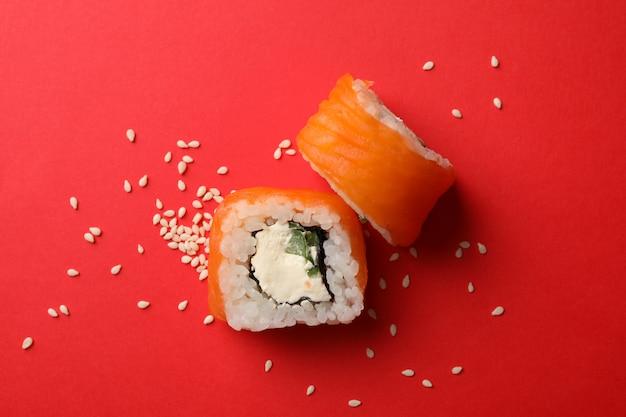 Deliciosos rollos de sushi en superficie roja. comida japonesa