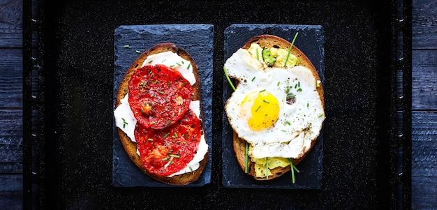 Deliciosos sabrosos huevos de aguacate y tostadas de queso con tomate