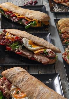 Deliciosos sándwiches de carne y variedad de ingredientes en mesa de madera