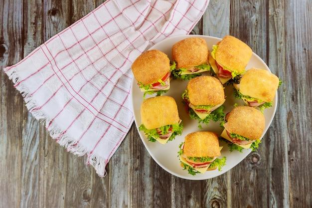 Deliciosos sándwiches en plato blanco sobre superficie de madera