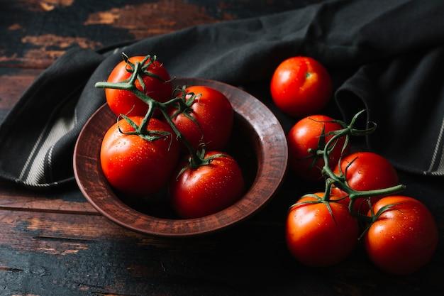 Deliciosos tomates frescos con tallos en mesa de madera
