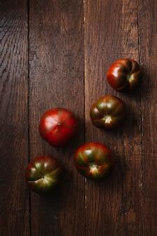 Deliciosos tomates en una vista superior de fondo de madera