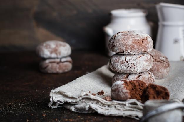 Deliciouse galletas crujientes de chocolate hechas en casa con azúcar en polvo en una mesa de piedra oscura