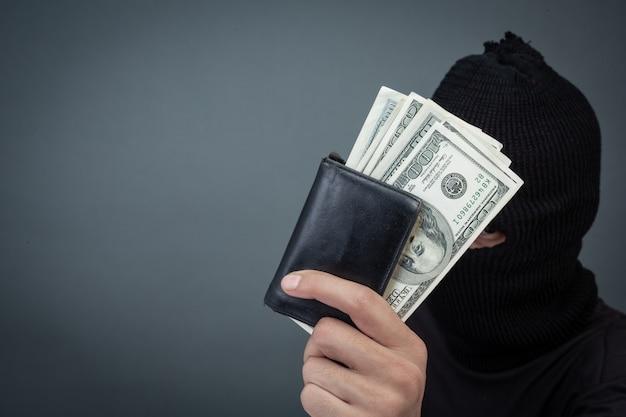 Los delincuentes negros llevan un hilo en la cabeza, sostienen una tarjeta de dólar en gris