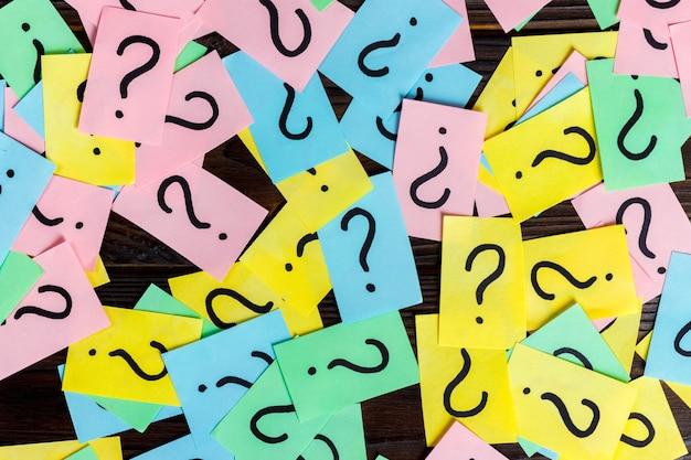 Demasiadas preguntas sobre fondo de madera. pila de notas de papel de colores con signos de interrogación. vista superior