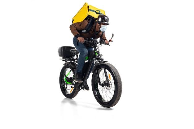 Demasiados pedidos. servicio de entrega sin contacto durante la cuarentena. el hombre entrega comida durante el aislamiento, con casco y mascarilla. tomando comida en bicicleta aislado en la pared blanca. seguridad. apresurándose.