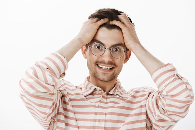 Demasiados pensamientos en un cerebro. hombre caucásico amistoso presionado con barba y bigote en gafas, tomados de la mano en la cabeza y sonriendo alegremente, tratando de mantenerse positivo mientras está agotado por el trabajo