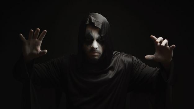 Demonio del infierno peligroso haciendo magia sobre fondo negro. disfraz y diseño de halloween