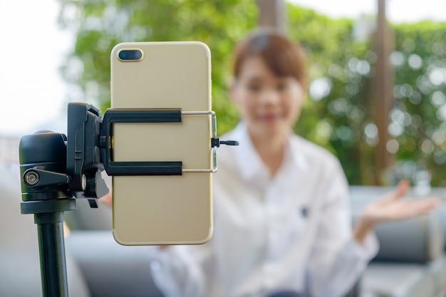 Demostración de los auriculares del desgaste de la mujer joven a través del vivo social o del selfie en el teléfono móvil móvil.