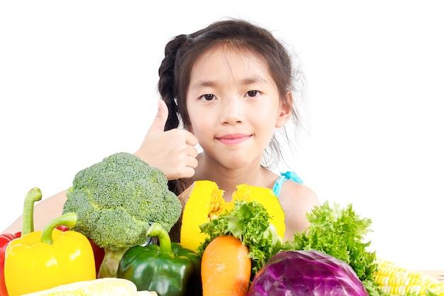 La demostración encantadora asiática de la muchacha disfruta de la expresión con las verduras coloridas frescas