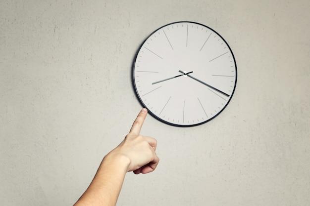 Demostración de la mano en el reloj redondo de la pared. de cerca