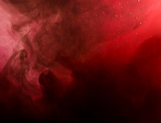 Densa nube roja de humo en el agua.
