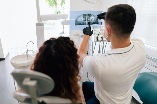 Dentista apuntando a la radiografía con el paciente