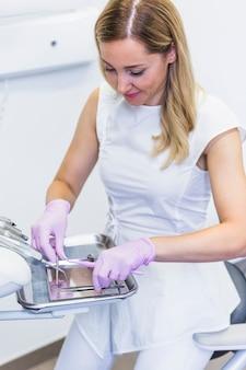 Dentista arreglando instrumentos dentales en clínica.
