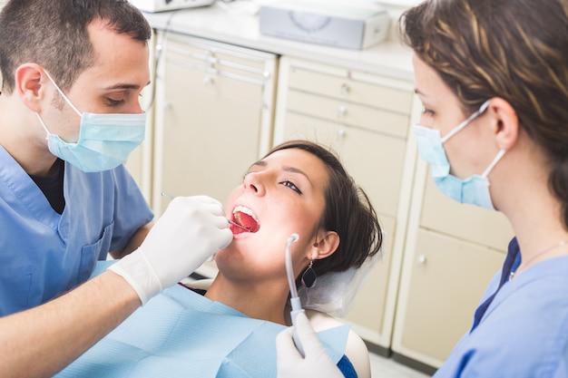 Dentista y asistente dental examinando los dientes del paciente.