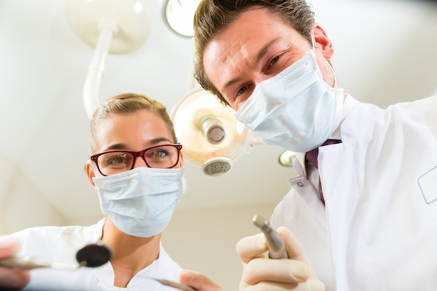 Dentista y asistente en un tratamiento, desde la perspectiva de un paciente.