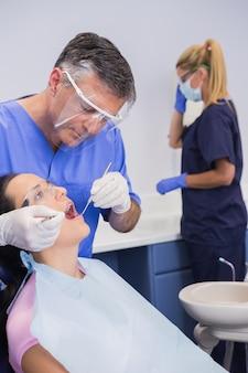 Dentista con careta y examinando a un paciente
