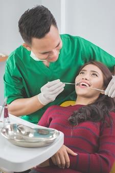 Dentista cuidando paciente femenino
