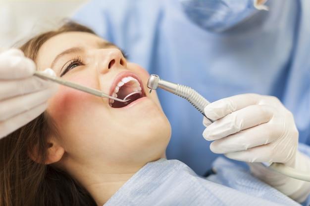 Dentista curando a una paciente