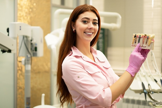 El dentista demuestra el diseño de los implantes. joven dentista en su lugar de trabajo, presentación de trabajo. diente enfermo, caries, pulpitis.